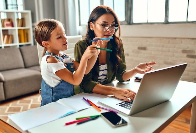 Zakenvrouw en moeder proberen op een laptop te werken wanneer haar dochtertje aan het spelen is en haar onderbreekt. freelance, thuiswerken.