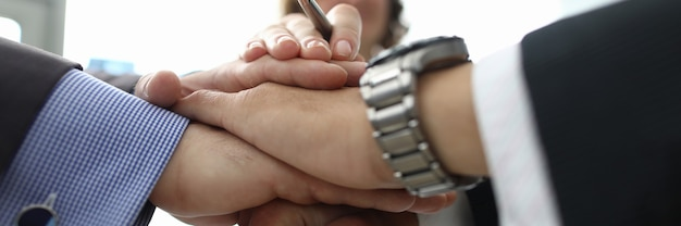 Zakenvrouw en twee zakenlieden vouwden hun handen samen in kantoorclose-up. sluiting van het concept van internationale overeenkomsten.