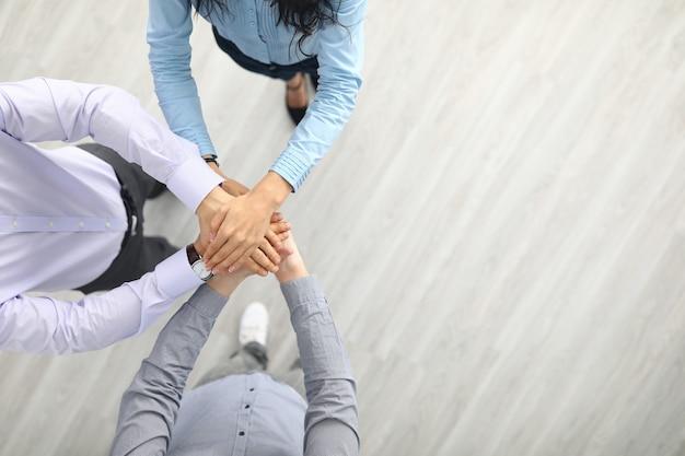 Zakenvrouw en zakenlieden staan samen met hun handen