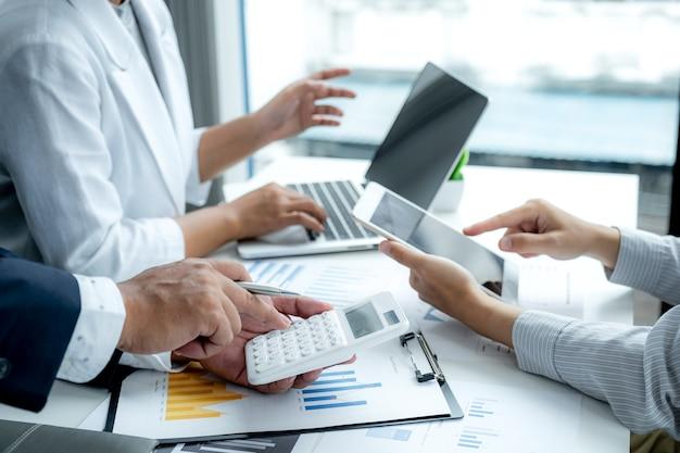 Zakenvrouw en zakenlieden teamvergadering om strategieën te plannen om het bedrijfsinkomen te verhogen. heb een brainstormgrafiekanalyse en bespreek het succes van het nieuwe doelwit.