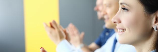 Zakenvrouw en zakenlieden zitten en klappen in hun handen