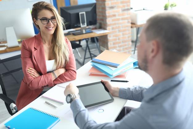 Zakenvrouw en zakenman bespreken bedrijfsprocessen aan de werktafel