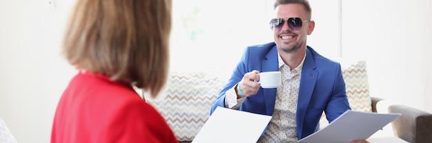 Zakenvrouw en zakenman drinken koffie en bespreken het ondertekenen van een overeenkomst