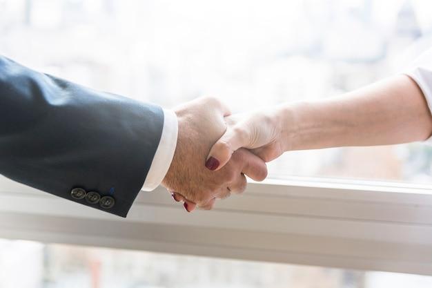 Zakenvrouw en zakenman handen schudden