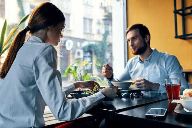 Zakenvrouw en zakenman met lunch aan een tafel in een café