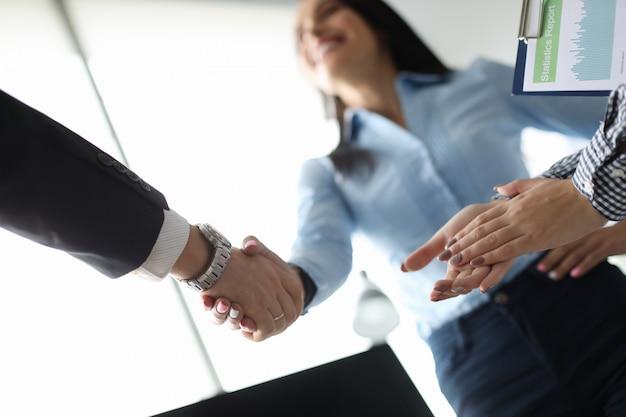 Zakenvrouw en zakenman schudden hand in ofiice