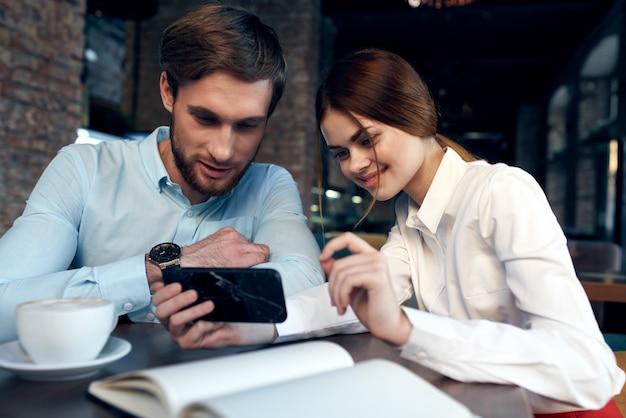 Zakenvrouw en zakenman smartphonescherm kijken aan een tafel in een café