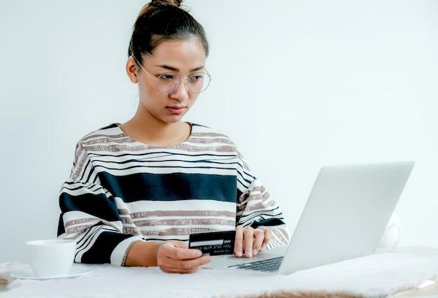 Zakenvrouw gebruik creditcard om online thuis te winkelen met laptop, betaling e-commerce, internetbankieren, geld uitgeven voor de volgende vakantie.