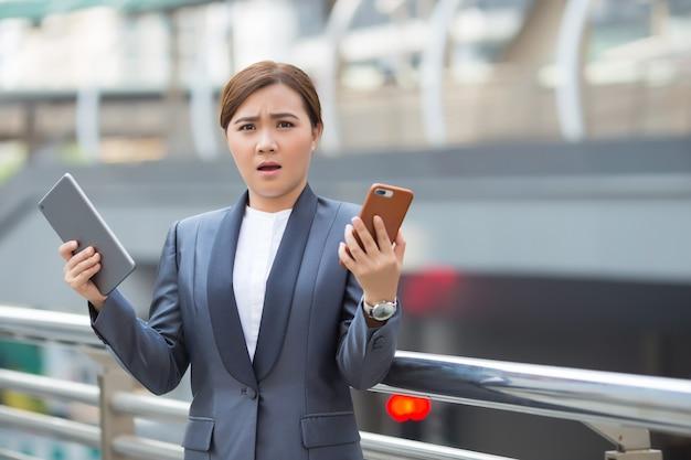 Zakenvrouw gebruik tablet en smartphone heeft verrassing