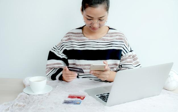Zakenvrouw gebruikt creditcard om thuis online te winkelen, e-commerce te betalen, internetbankieren, geld uit te geven voor de volgende vakantie.