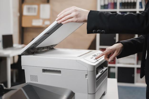 Zakenvrouw gebruikt de printer om documenten te scannen en af te drukken
