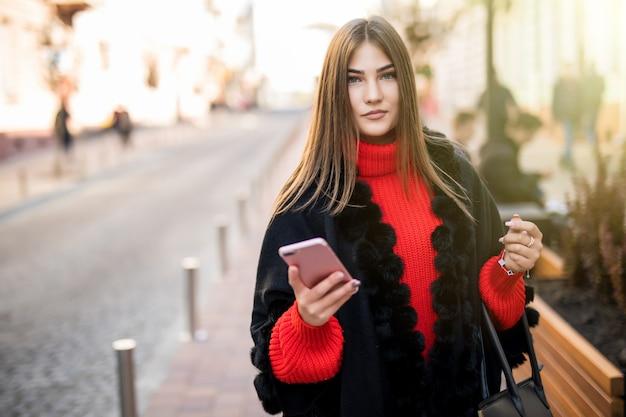 Zakenvrouw gebruikt smartphone op straat tijdens het lopen