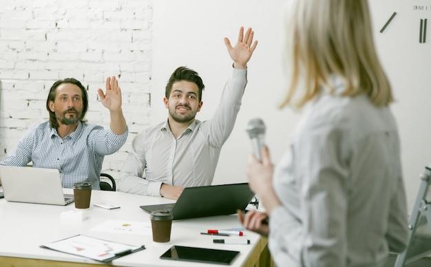 Zakenvrouw geeft presentatie of seminar in kantoor. de vrouw die een microfoon hield, wendde zich tot haar collega's die bij bureau in bureau zitten en hun handen opheffen om vragen over haar toespraak te stellen