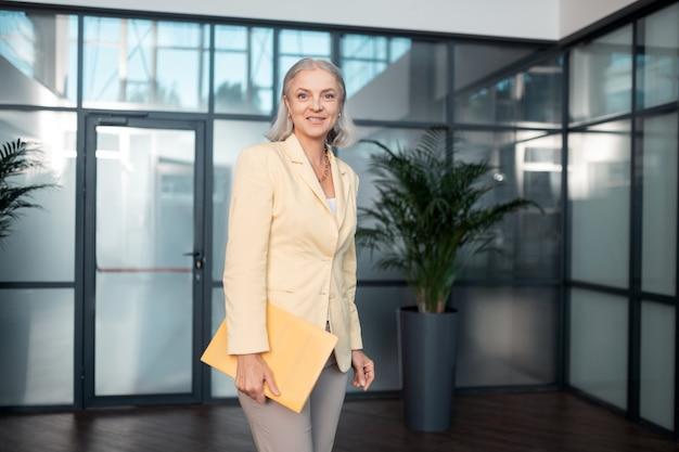 Zakenvrouw. glimlachende senior zakenvrouw in stijlvolle kantoorkleding met een papieren map terwijl ze voor haar kijkt