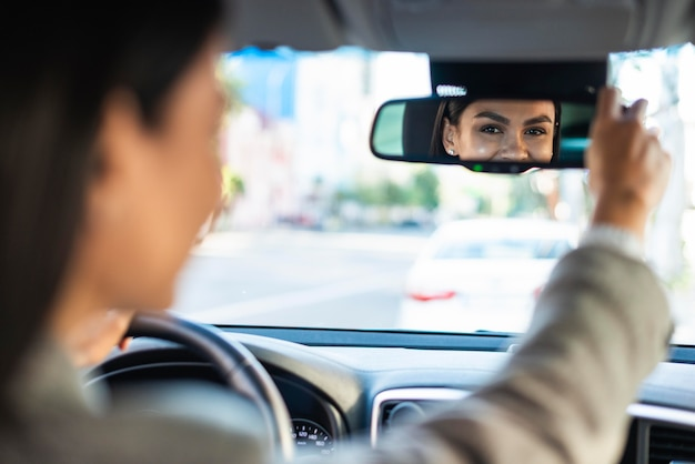 Zakenvrouw haar achteruitkijkspiegel auto aanpassen