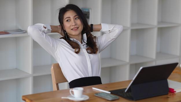 Zakenvrouw haar armen strekken na een drukke dag op het werk, zakenvrouw rust nemen