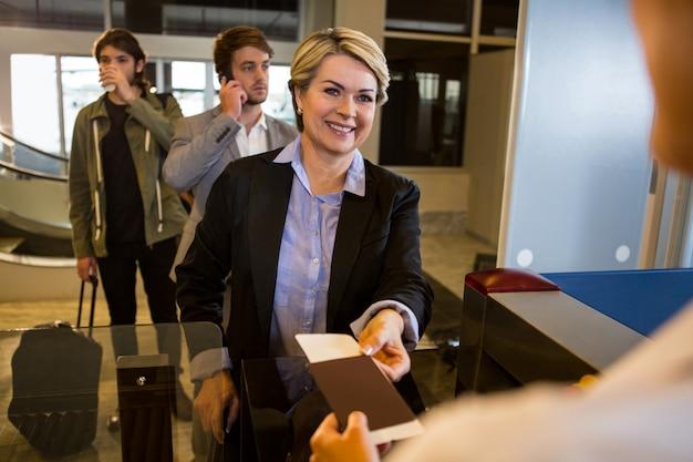 Zakenvrouw haar instapkaart overhandigen aan het vrouwelijk personeel