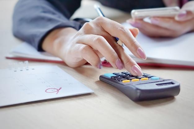 Zakenvrouw hand haar maandelijkse uitgaven berekenen tijdens belastingseizoen