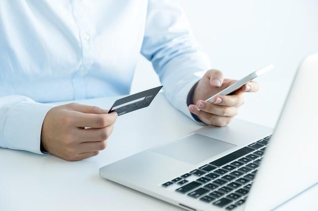 Zakenvrouw hand houden en creditcard gebruiken om online te winkelen