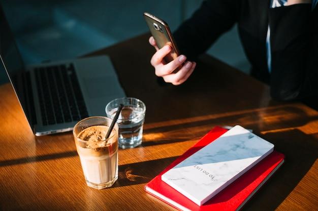 Zakenvrouw hand met behulp van mobiele telefoon met laptop; chocolademilkshake en boeken over houten bureau