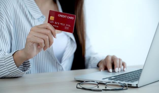 Zakenvrouw hand met creditcard om online te winkelen vanuit huis, betaling e-commerce, internetbankieren, geld uitgeven voor de volgende vakantie.