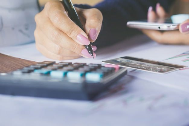 Zakenvrouw hand schrijven en het berekenen van haar maandelijkse uitgaven