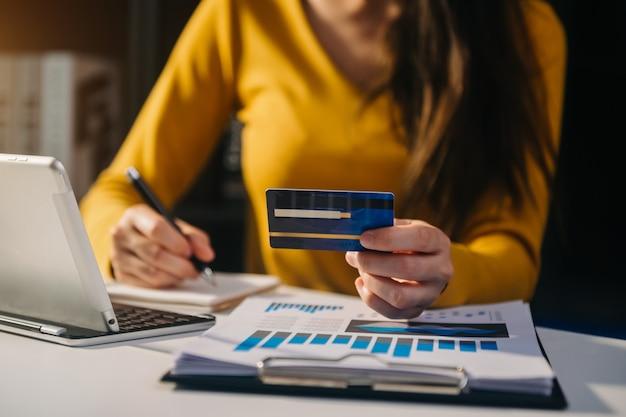 Zakenvrouw handen gebruikend smartphone en houden creditcard met digitaal laageffect diagram als online winkelconcept