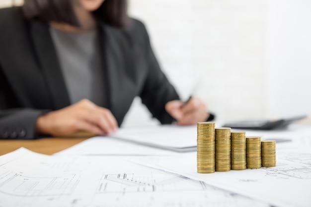 Zakenvrouw herziening document met geld en blauwdrukken op de tafel