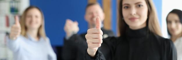 Zakenvrouw houdt duimen omhoog tegen de achtergrond van werknemers in functie. succesvol team bedrijfsconcept