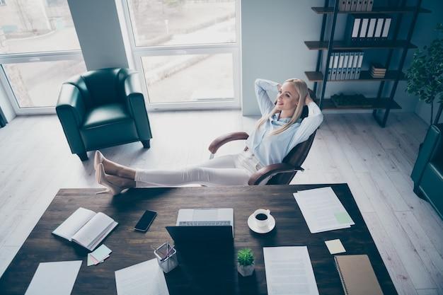 Zakenvrouw houdt handen achter hoofd benen bureau