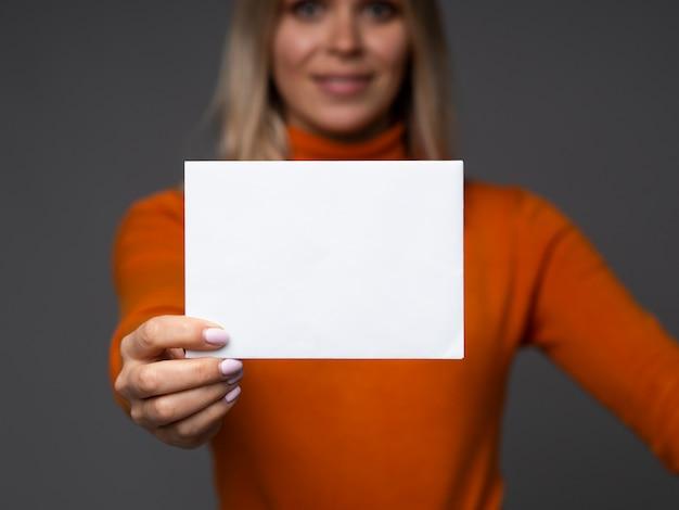 Zakenvrouw houdt leeg kaartmodel met ruimte voor tekst op een grijze achtergrond.