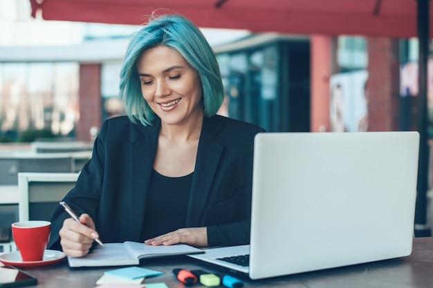 Zakenvrouw iets schrijven terwijl ze haar laptop gebruikt en in een coffeeshop zit