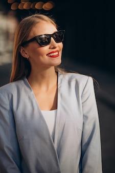 Zakenvrouw in blauwe jas bij het kantoorcentrum