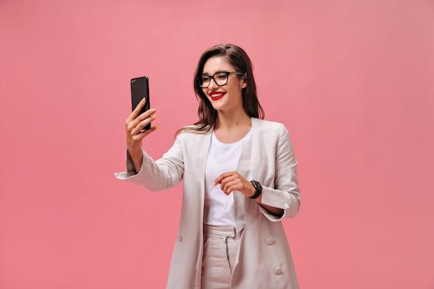 Zakenvrouw in brillen en pak neemt selfie op roze achtergrond. blij charmant meisje met lang donker haar met rode lippenstift maakt foto.
