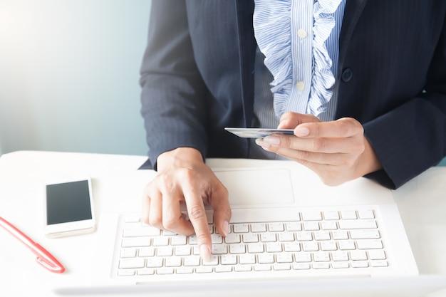 Zakenvrouw in donker pak bedrijf creditcard en met behulp van laptop, business en online winkelen concept