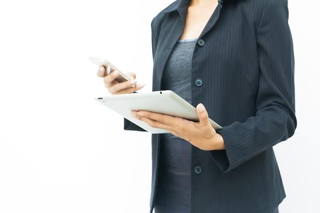 Zakenvrouw in donker pak met behulp van haar tablet en mobiele telefoon op een witte achtergrond met kopie ruimte