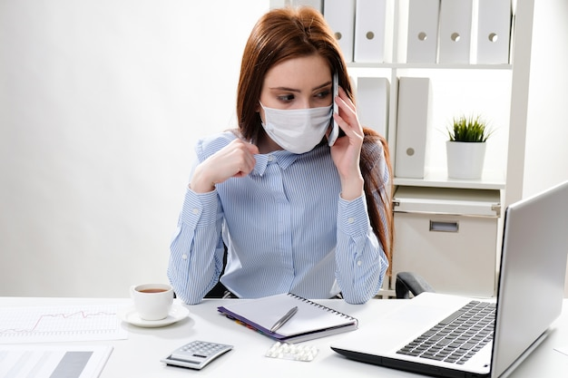 Zakenvrouw in een masker op de werkplek praten aan de telefoon