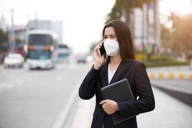 Zakenvrouw in een pak dragen van beschermende gezichtsmasker