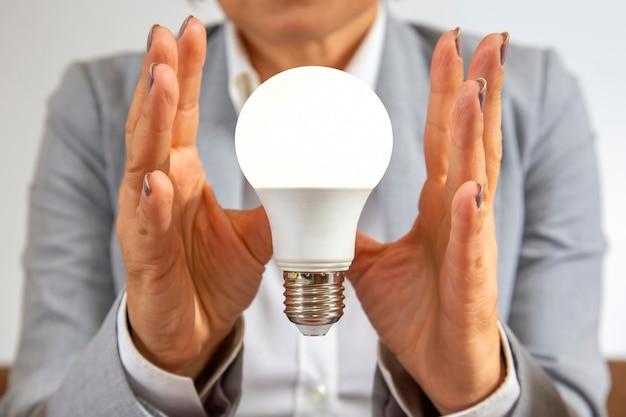 Zakenvrouw in een pak heeft een ingeschakelde elektrische lamp in haar handen