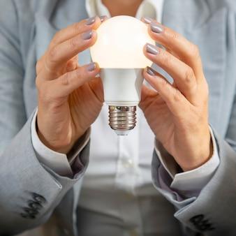 Zakenvrouw in een pak houdt een ingeschakelde elektrische lamp in haar handen in close-up