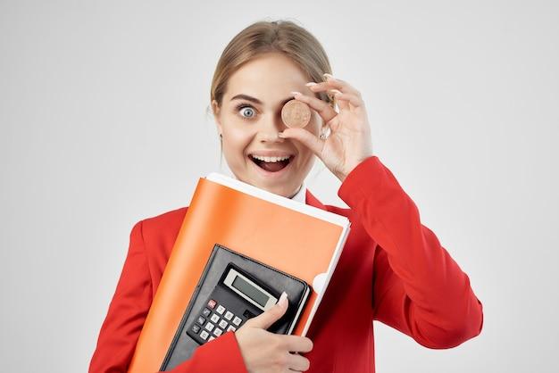Zakenvrouw in een rood jasje met documenten in de hand lichte achtergrond. hoge kwaliteit foto