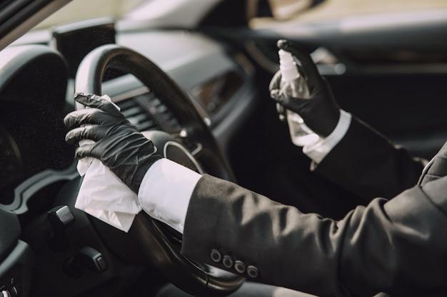 Zakenvrouw in een zwart masker zitten in een auto