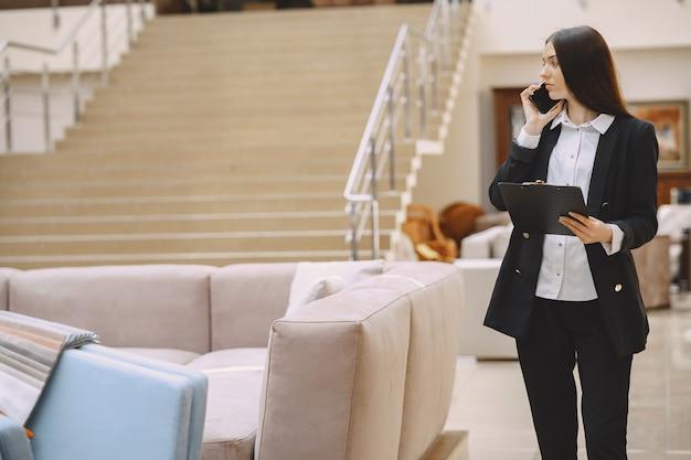 Zakenvrouw in een zwart pak in het kantoor
