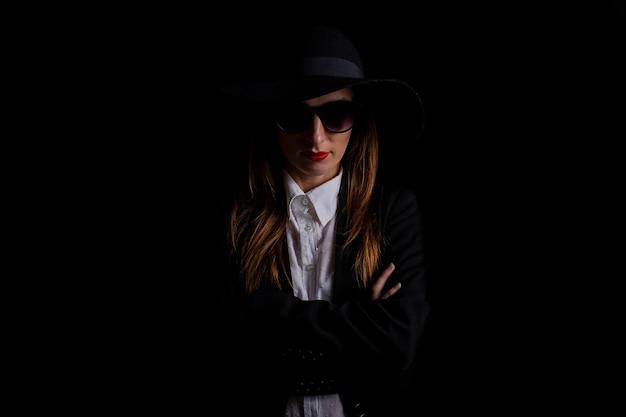 Zakenvrouw in een zwarte hoed, bril op een zwarte.