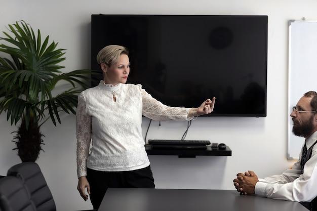 Zakenvrouw in formeel overhemd met de middelvinger conflict tussen twee werknemers: zakenvrouw toont aan haar boze en woedende baas (joodse man in keppeltje) middelvingergebaar.
