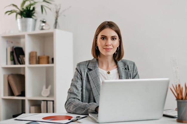 Zakenvrouw in geruit jasje met glimlach zittend aan een bureau in haar kantoor.