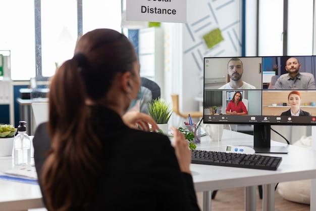 Zakenvrouw in gesprek met externe business team tijdens online videocall