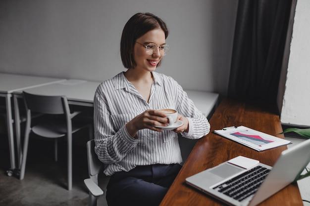 Zakenvrouw in gestreept shirt genieten van haar ochtendkoffie terwijl ze naar haar computerscherm kijkt.
