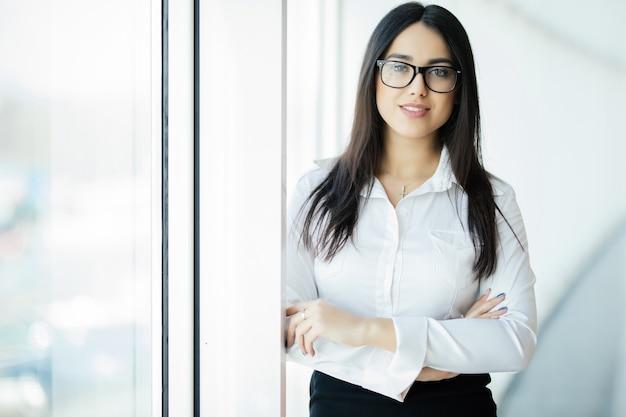 Zakenvrouw in glazen gekruiste handen portret in kantoor met panoramische ramen. bedrijfsconcept