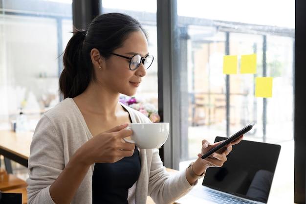 Zakenvrouw in glazen met koffiekopje en het gebruik van mobiele telefoon.